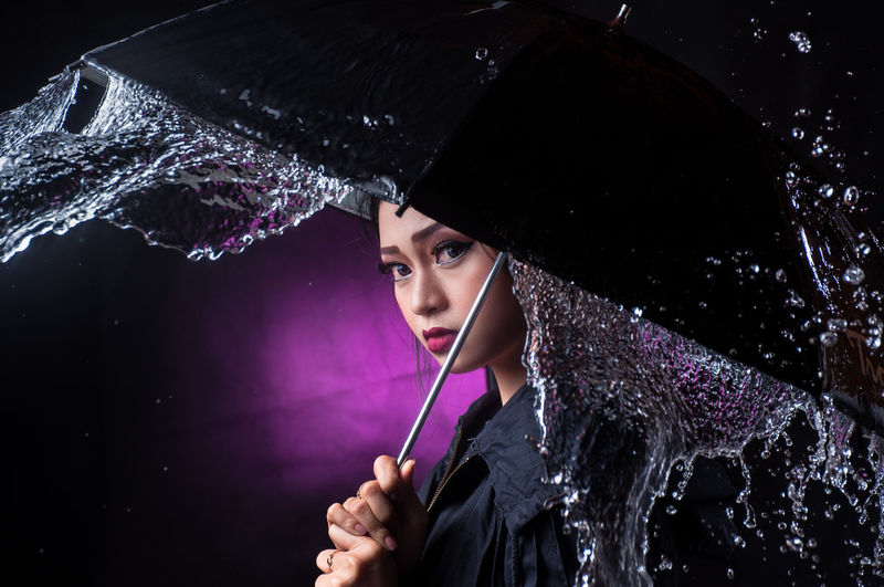 Portrait of young woman holding wet umbrella against purple background