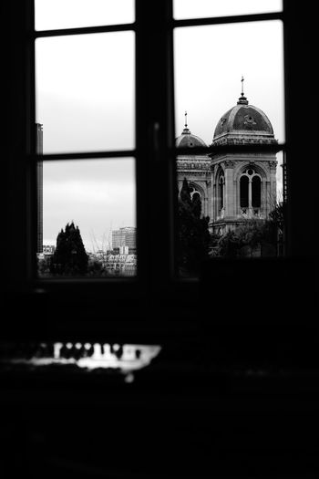 View of historic building against sky seen through window
