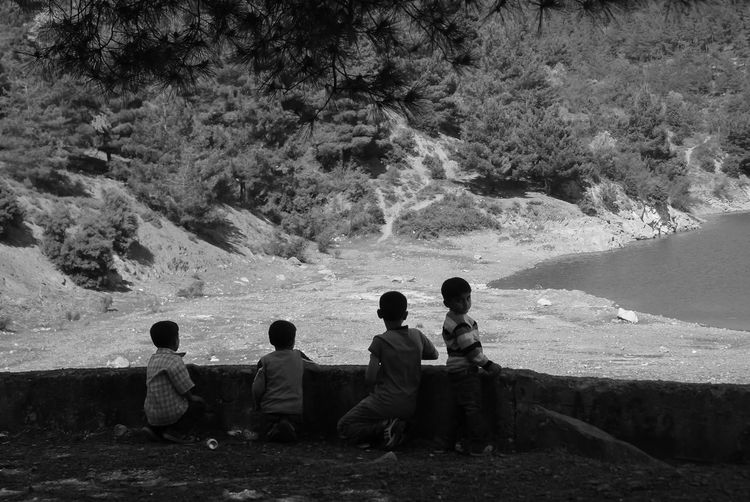 Beauty In Nature Blackandwhite Boys Childhood Day Friendship Full Length Kids4ever Leisure Activity Lifestyles Live For The Story Men Nature Outdoors People Real People Rear View Sitting Standing Togetherness Tree Water Women