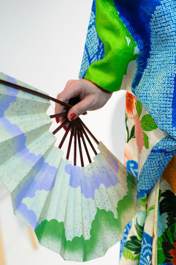 Low angle view of hand holding multi colored umbrella