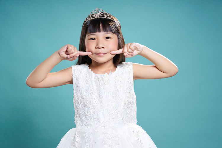 Portrait of girl wearing crown while standing against turquoise background