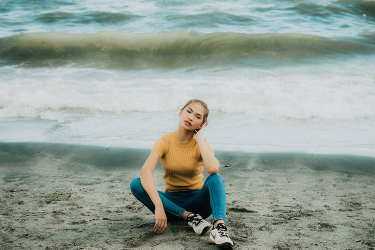 Portrait of young woman sitting on beach