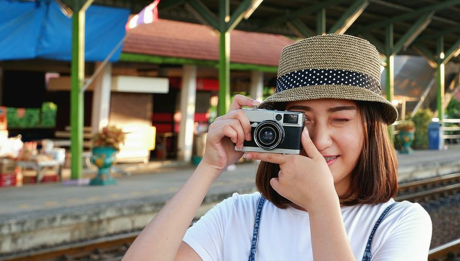 Young Asian female tourist with bamboo hat taking photo with vintage camera on railroad platform at train station, lifestyle in travel concept Female Asian  Casual Beauty Portrait Traveler Taking Photo Smiling Lifestyle Railway Platform Train Station Bamboo Hat Vintage Tone Travel Tourist Pretty Happiness Outdoors Enjoy EyeEm Selects Technology Photography Themes Wireless Technology Portrait Photographing Headshot Young Women Camera - Photographic Equipment Photographer Close-up