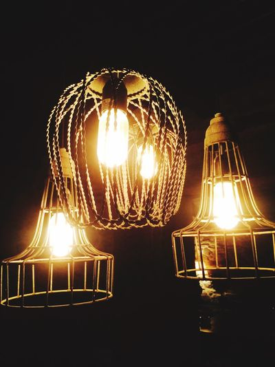 Low angle view of illuminated lamp in row at night