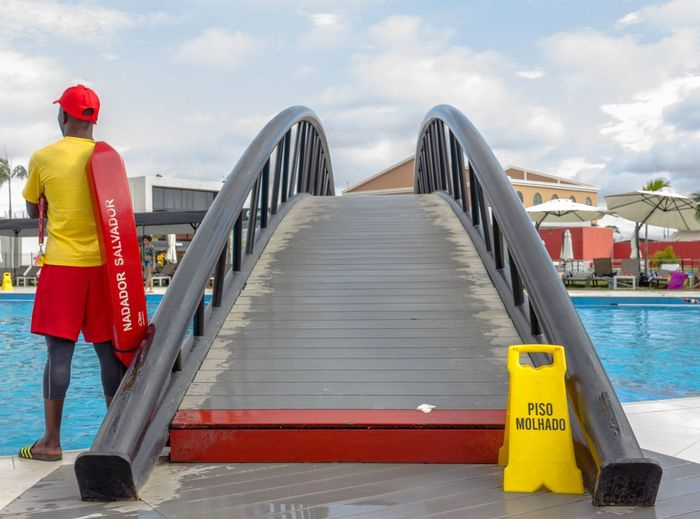 Pool guard Angola Luanda Africa Bridge Clouds Day Hardhat  Men One Person Outdoors Pool Pool Guy Railing Real People Rear View Sky Summer Warning Water Be. Ready.