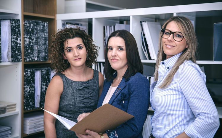 Portrait of three businesswomen working in the office and smiling at camera Business Company Horizontal Office Standing Teamwork Woman Working Business Finance And Industry Businessman Businesswoman Caucasian Chief Female Folder Headquarters Job Leadership People Portrait Smiling Sucess Team Three People Training