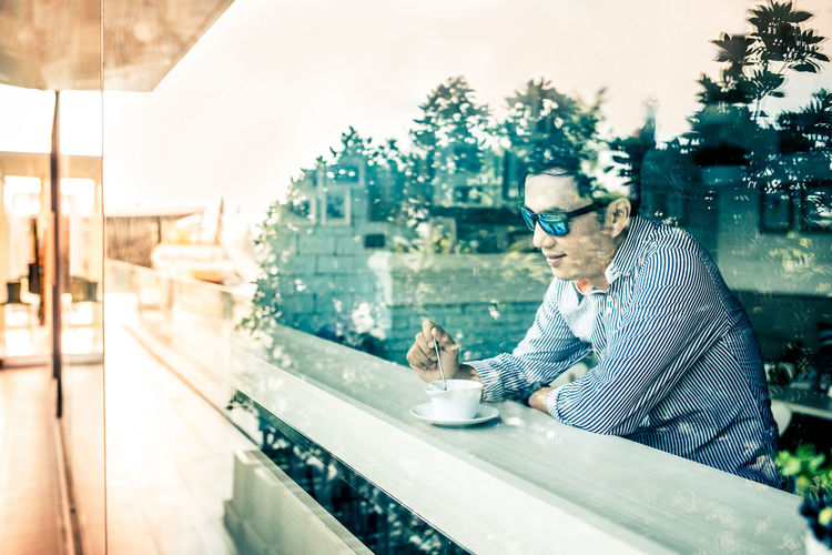 Coffee break. Close-up image of handsome asian man in casual dressed holding cup of coffee while sitting at the rustic wooden table, taking photo again window.lifestyle concept. Lifestyle Adult Business Businessman Cafe City Coffee Coffee - Drink Coffee Break Cup Drink Drinking Fashion Food And Drink Freelance Glasses Lifestyles Men Mug Nomadic One Person Outdoors Refreshment Sitting Table