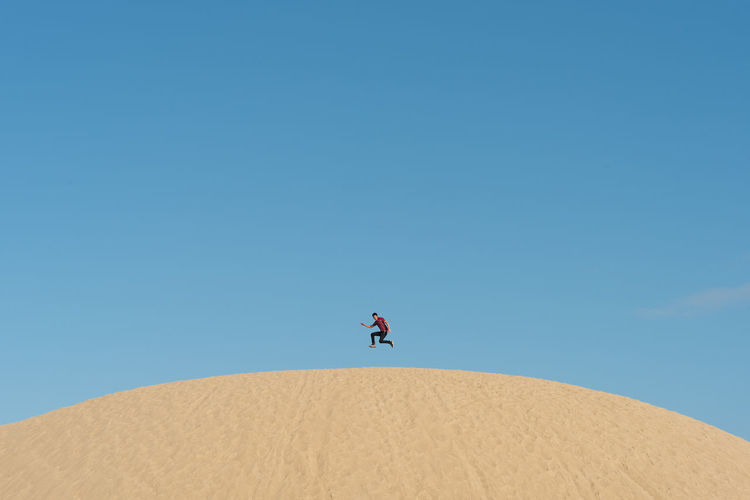 Low angle view of man jumping over desert against clear sky