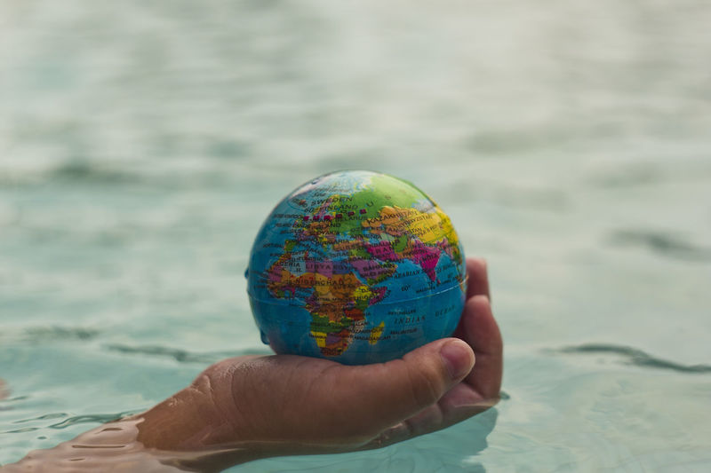 Above close up looking down on hand holding the world over water Hand Holding Hands India Map Middle East Plant Power Africa Cat Continent Ecology Energy Europe Ocean Planet Protection Sustainability Sustainable Sustainable Resources Water World