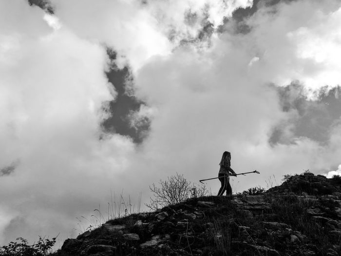 Low angle view of woman walking with stick on mountain against cloudy sky