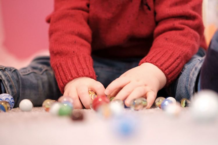 Midsection of boy playing with marbles