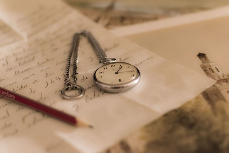 High angle view of pocket watch and pencil on letter