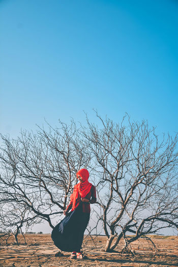 Woman in hijab standing by bare tree on land