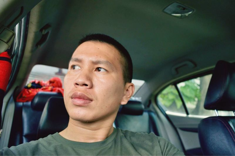 Young man looking away while sitting in car