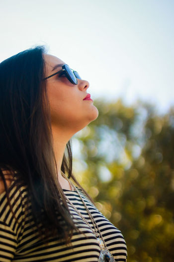 Close-up of woman in sunglasses against sky