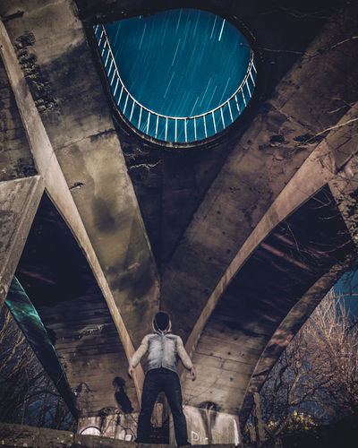 Low Angle View Of Man Standing Under Bridge