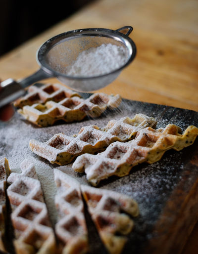 High angle view of powdered sugar sprinkling on waffle