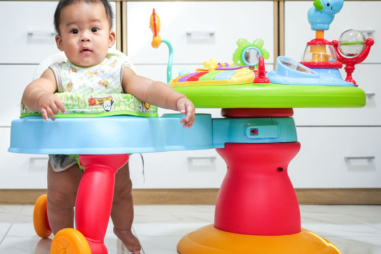 Cute baby girl sitting on table at home