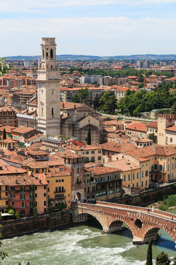 Verona cathedral by buildings and bridge over river