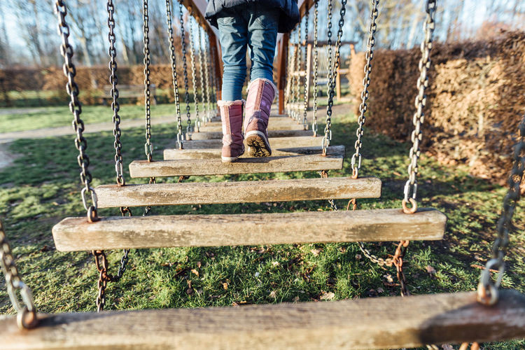 Low Section Of Child Walking On Play Equipment