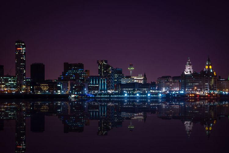 Reflection of illuminated city on calm lake at night