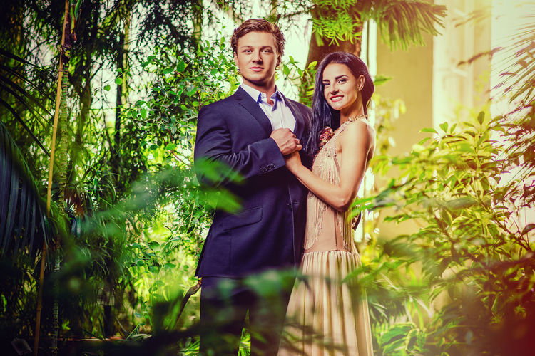Portrait Of Smiling Bride And Groom Holding Hands While Standing Amidst Plants