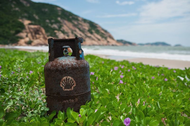 Abandoned gas canisters Gas Canister Abandoned Things Abandoned Nature Focus On Foreground Plant Sky No People Close-up Mountain Beauty In Nature Green Color Field Water Grass Growth Flower Outdoors Tranquil Scene