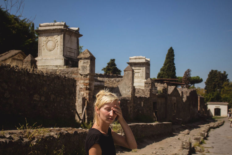 Woman standing against historic building at pompeii during sunny day