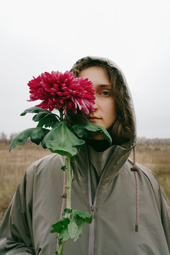 Flowering Plant One Person Portrait Nature Lifestyles Portrait Of A Woman Woman Portrait Sad Sadness Autumn Flower Plant Front View Looking At Camera Real People Beauty In Nature Outdoors Girl Standing Holding Flower Head Sad Girl Casual Clothing Fall Calm Autumn Mood