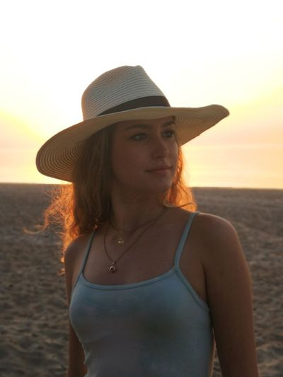 Portrait of beautiful woman standing on beach against sky during sunset