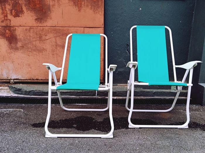 Empty chairs against blue wall
