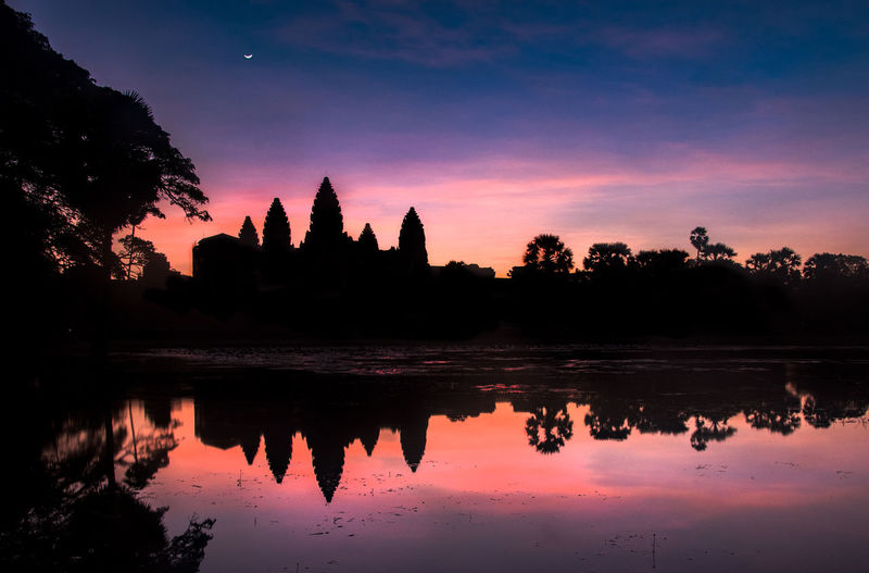 Silhouette angkor wat temple and trees reflecting on lake against sky during sunrise