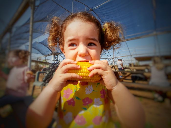 Close-Up Of Cute Girl Eating Corn While Standing Outdoors