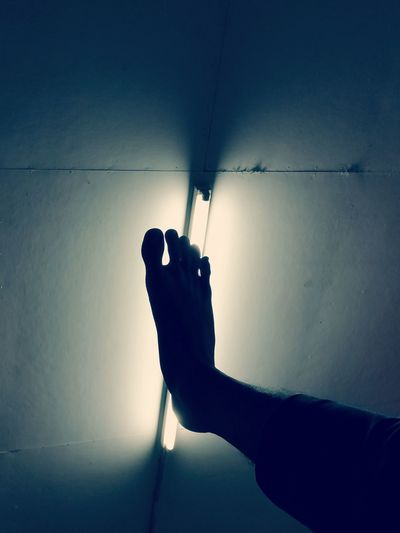 Close-up of hand holding shadow on wall