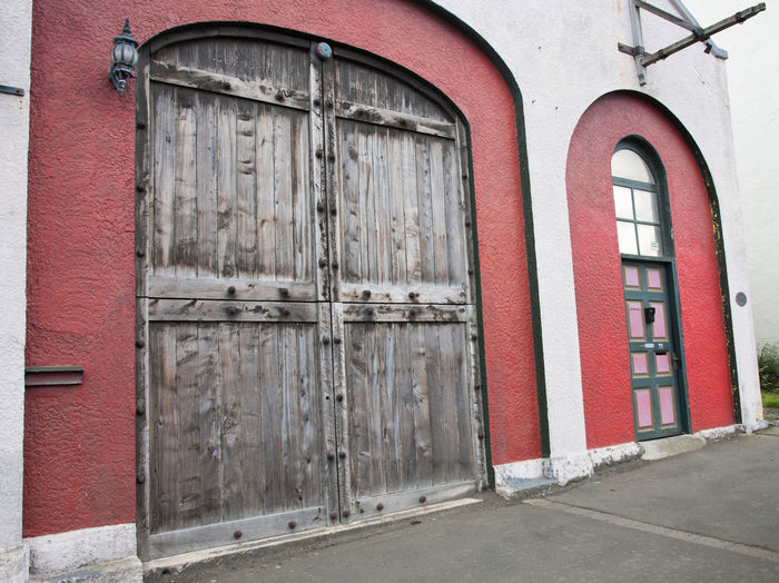 Port Chalmers, Dunedin, New Zealand-December 11,2016: Port stables rustic door entrance in downtown Port Chalmers, Dunedin, New Zealand Downtown Dunedin Façade Rustic Arch Architectural Feature Architecture Brick Red Building Building Exterior Built Structure City Craftsmanship  Door Downtown District Entrance New Zealand Port Chalmers Port Stable Red Town Travel Destinations Wall Wood - Material Woodworking