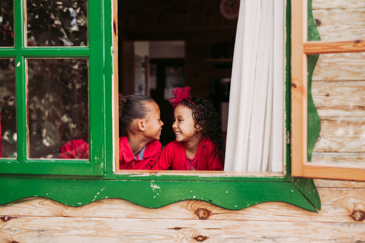 Portrait of mother and girl sitting on window