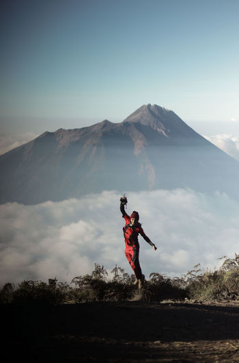 Man with arms raised on mountain against sky