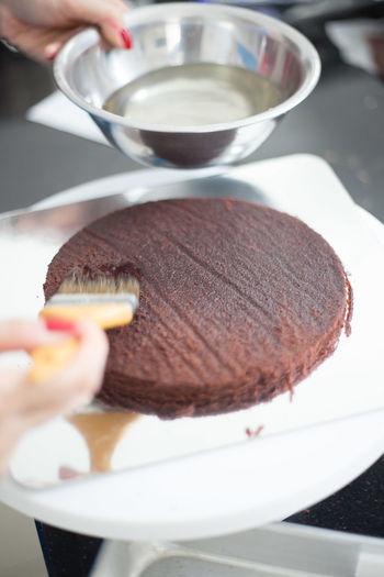 Cropped image of hand applying syrup on sponge cake