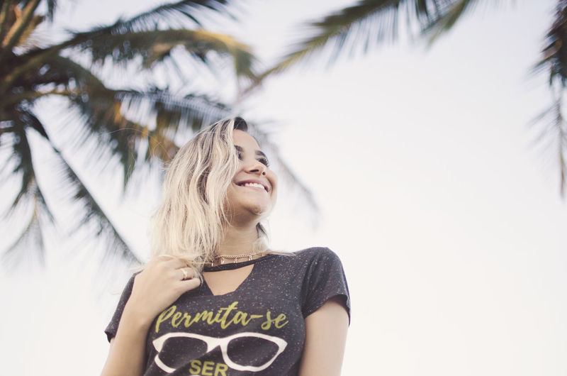 One Person Happiness Emotion Smiling Tree Women Front View Tropical Climate Leisure Activity Lifestyles Casual Clothing Palm Tree Day Plant Real People Portrait Adult Young Adult Outdoors Beautiful Woman Hairstyle Beach Blonde Happiness Fun