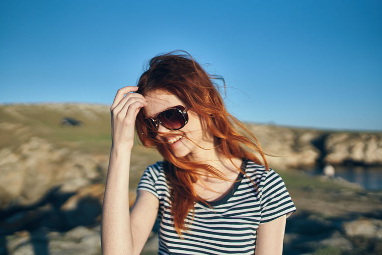 Midsection of woman wearing sunglasses against sky