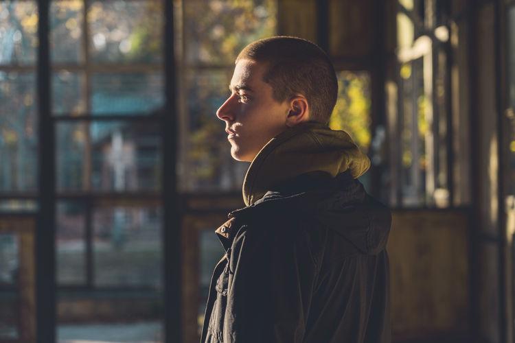 Side view of boy looking away against window