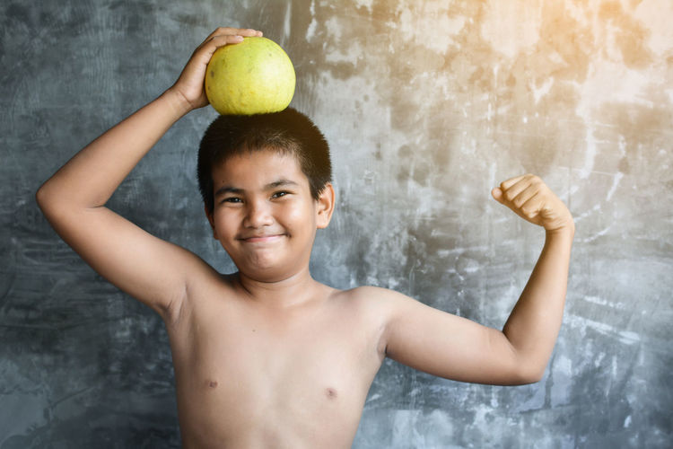 Portrait of smiling shirtless boy holding food while standing against wall