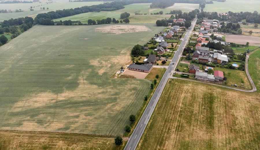 Aerial view of a village suburb in the rural area of Saxony-Anhalt Aerial Aerial View Agriculture Architecture Beauty In Nature Countryside Day Drop Environment Field Grass Growth High Angle View Land Landscape Nature No People Outdoors Patchwork Landscape Plant Rural Scene Scenics - Nature Transportation Tree