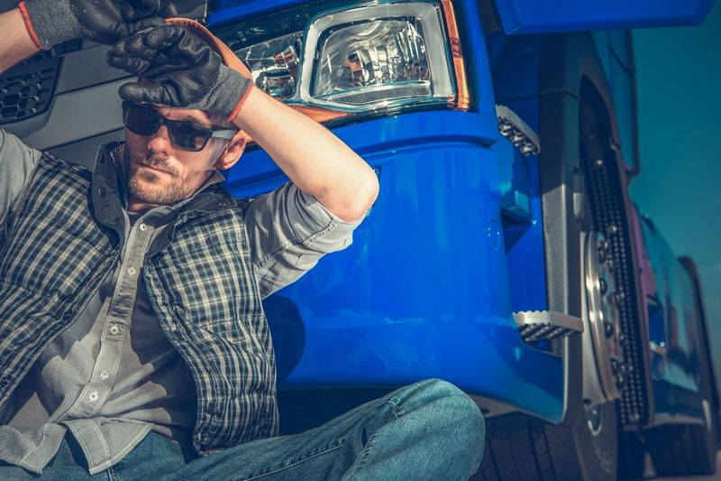 Low angle view of man sitting by truck