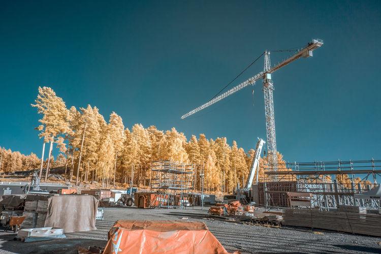 Cranes at construction site against sky
