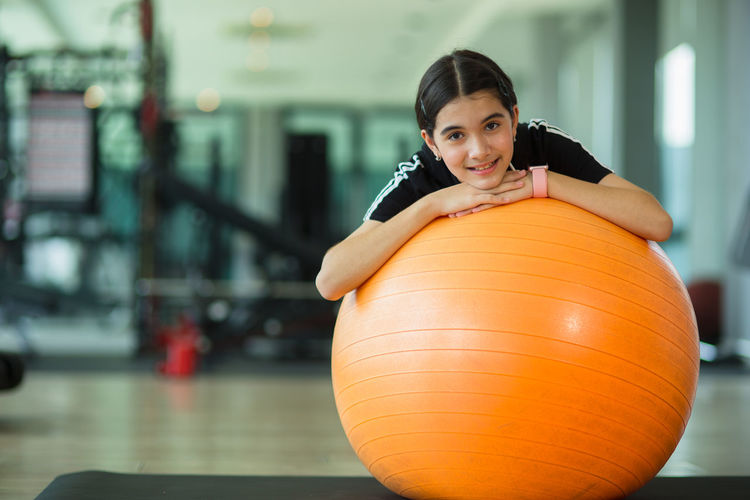 Portrait of girl with fitness ball at gym