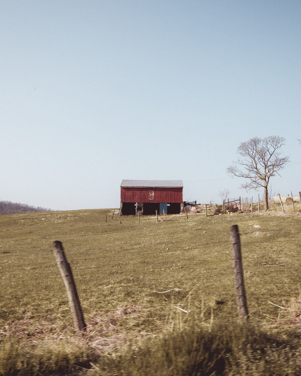 field, clear sky, landscape, built structure, grass, agriculture, architecture, no people, day, tranquility, outdoors, barn, rural scene, tree, building exterior, nature, bare tree, scenics, sky, beauty in nature
