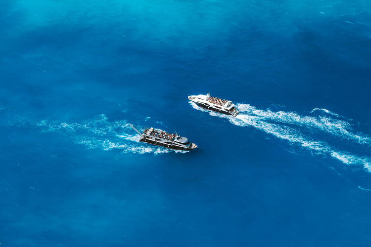 High angle view of sailboats sailing in sea