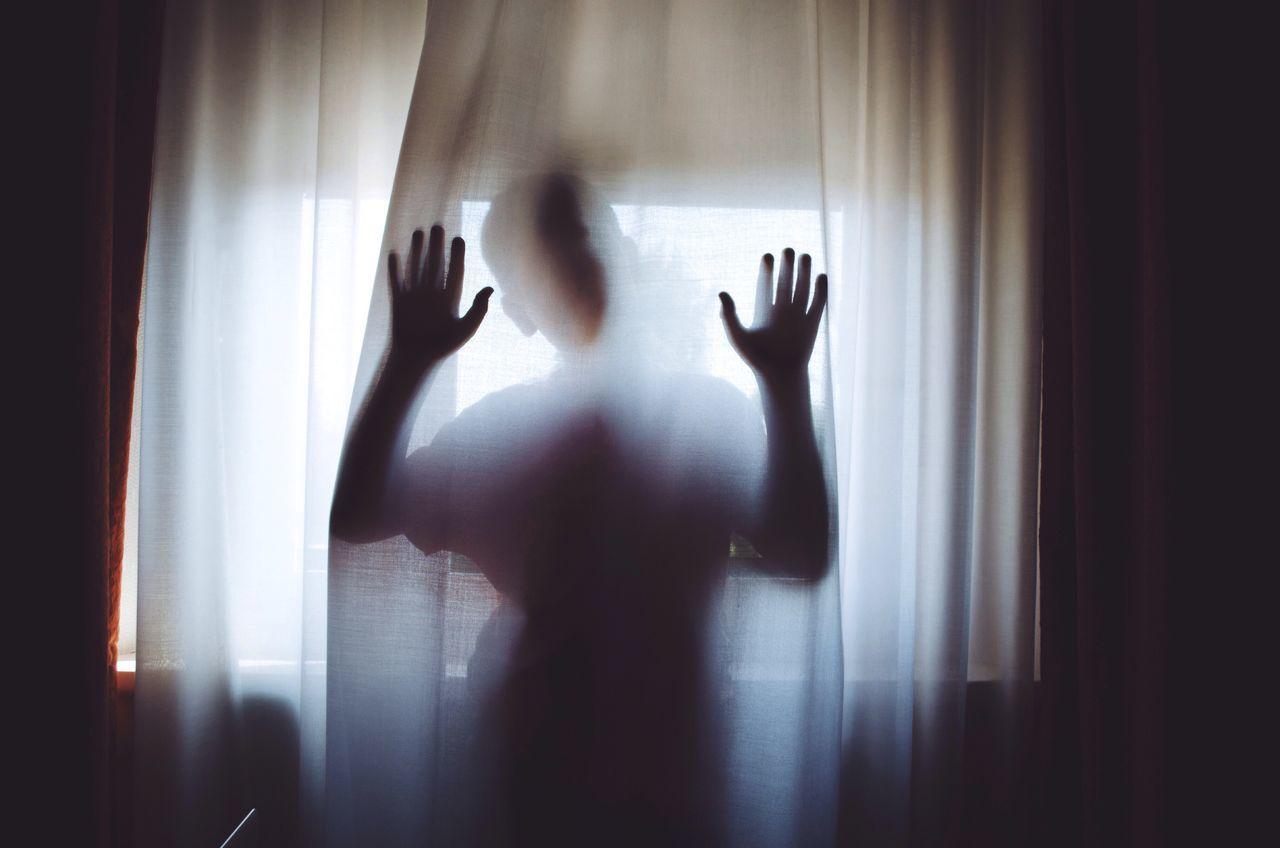 Boy hiding behind curtain at home