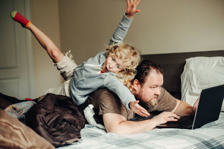 Father and son on bed at home